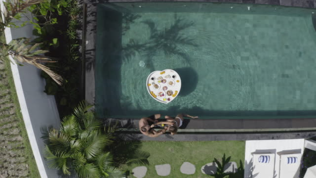 aerial drone view of a woman swimming in a pool at a villa resort hotel traveling in exotic tropical bali, indonesia. - bali stock videos & royalty-free footage