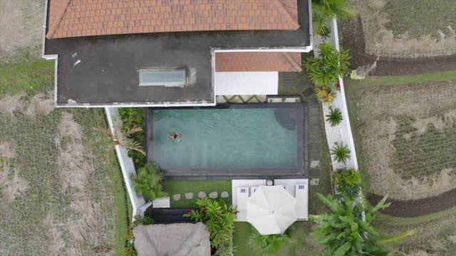 aerial drone view of a woman swimming in a pool at a villa resort hotel traveling in exotic tropical bali, indonesia. - zen like stock videos & royalty-free footage