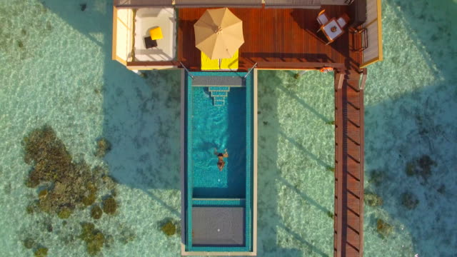 Aerial drone view of a woman swimming in a pool of an overwater bungalow on a tropical island resort hotel.