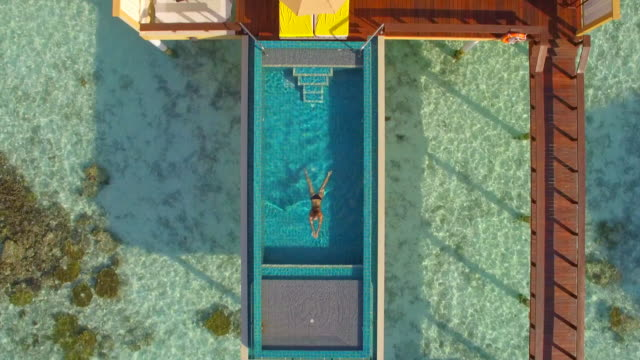vídeos de stock, filmes e b-roll de aerial drone view of a woman swimming in a pool of an overwater bungalow on a tropical island resort hotel. - hotel de luxo