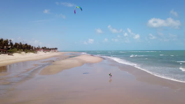 Aerial drone view of a woman walking after kiteboarding on a kite board.