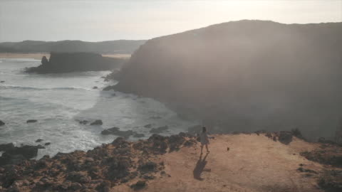 stockvideo's en b-roll-footage met aerial drone view of a woman walking on a cliff above a beach. - slow motion - klif