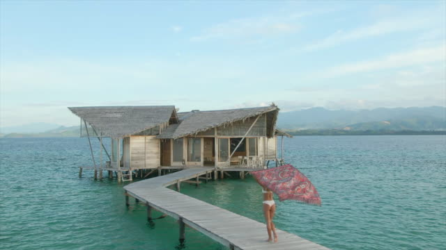 vidéos et rushes de aerial drone view of a woman walking to her over water bungalow hut with a sarong on a deck at tropical island hotel resort. - sarong
