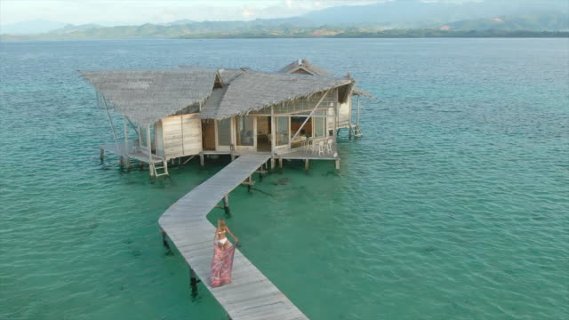 aerial drone view of a woman walking to her over water bungalow hut with a sarong on a deck at tropical island hotel resort. - sarong stock-videos und b-roll-filmmaterial