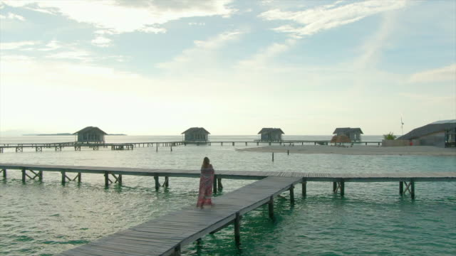 vidéos et rushes de aerial drone view of a woman walking with a sarong on a deck at tropical island in over water bungalow hotel resort. - sarong