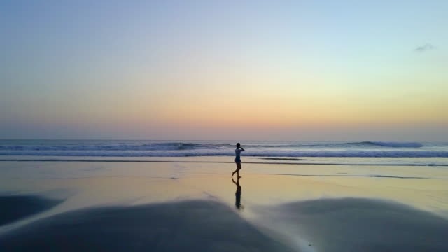 vidéos et rushes de aerial drone view of a young woman walking on the beach at sunset. - silhouette