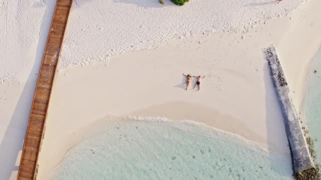 vídeos y material grabado en eventos de stock de aerial drone view of adult couple lying down on a beach, maldives - acostado