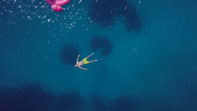aerial drone view of and man and two women on inflatable flamingos, sailing in skiathos, greece. - time-lapse - drei personen stock-videos und b-roll-filmmaterial
