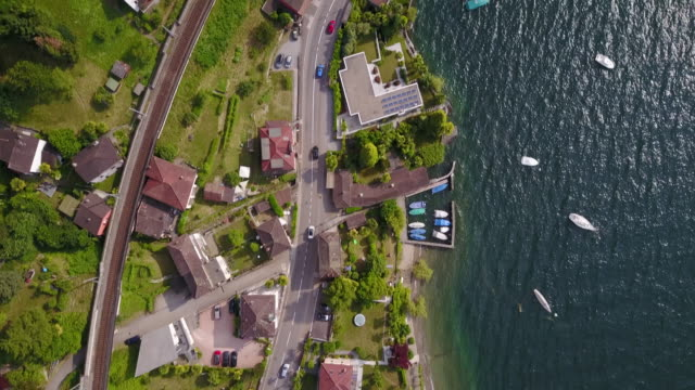 aerial drone view of cars driving in a town near lake maggiore, switzerland. - ticino canton stock videos and b-roll footage