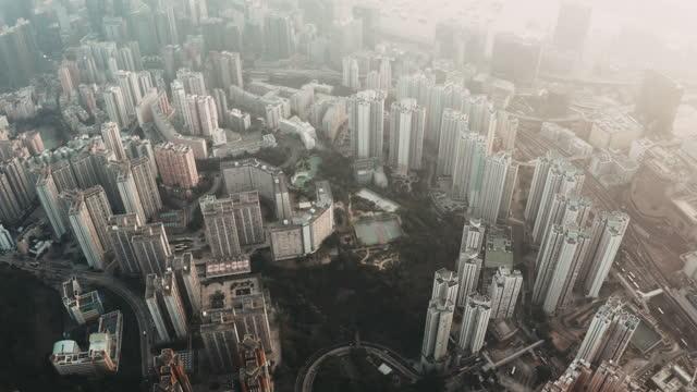 vídeos de stock, filmes e b-roll de vista aérea de drones dos edifícios da cidade em dia nebuloso - kowloon
