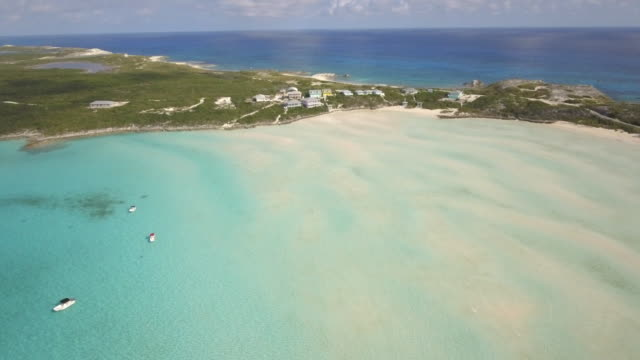 vídeos y material grabado en eventos de stock de aerial drone view of clear water and houses on a tropical island beach and coast in the bahamas, caribbean. - bahamas
