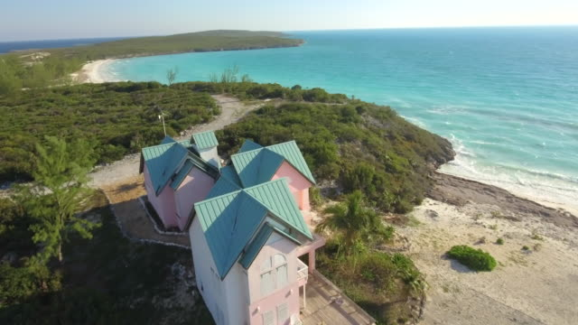 vidéos et rushes de aerial drone view of clear water and houses on a tropical island beach and coast in the bahamas, caribbean. - bahamas