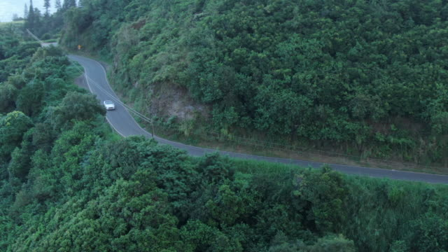 aerial drone view of convertible car ascending windy mountain road - bergstrecke stock-videos und b-roll-filmmaterial
