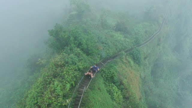 vidéos et rushes de vue aérienne drone de couple monter un escalier raide vers le haut de la montagne à travers le brouillard - s'évader du réel