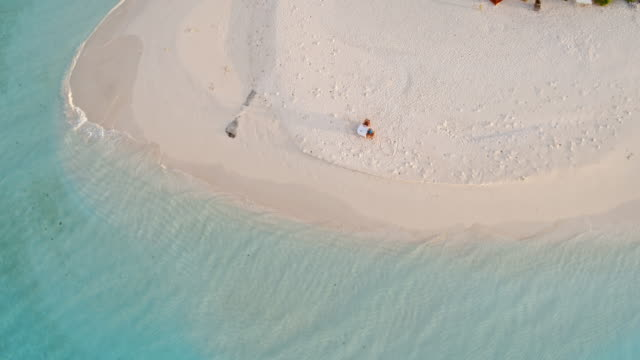 Aerial drone view of couple eating on the beach, Maldives