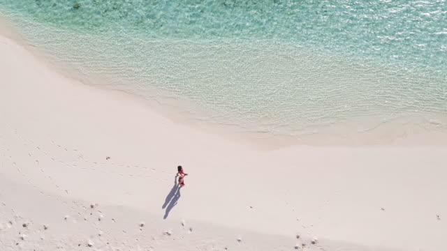 Aerial drone view of couple walking on the beach
