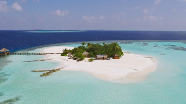 Aerial drone view of deserted tropical island in the turquoise sea of the Maldives