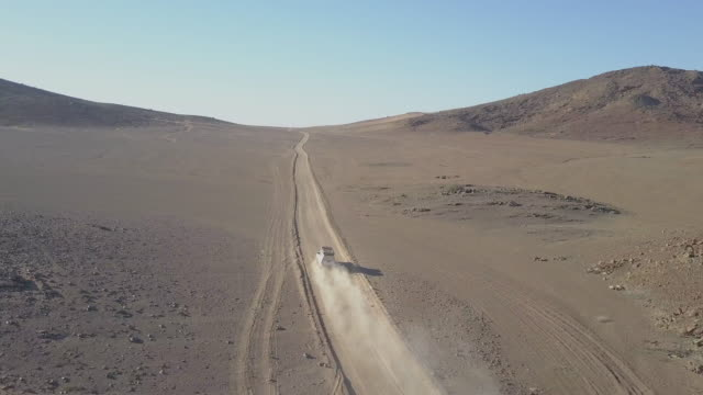 vídeos de stock, filmes e b-roll de aerial drone view of driving a pickup truck on a dirt road desert in africa. - time-lapse - áfrica meridional