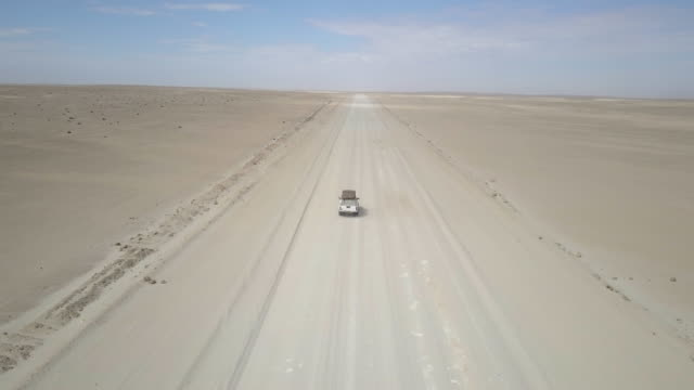 aerial drone view of driving a pickup truck on a dirt road desert in africa. - time-lapse - identity stock videos & royalty-free footage