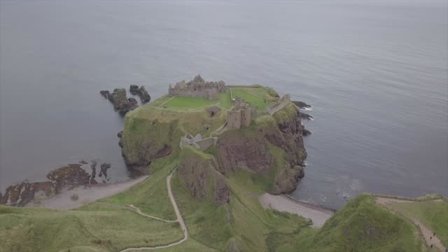 aerial drone view of dunnotar castle in a cloudy day - スコットランド点の映像素材/bロール