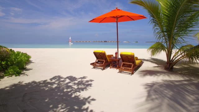 vídeos de stock, filmes e b-roll de aerial drone view of empty beach chairs and umbrella on a tropical island in the maldives. - cadeira de praia