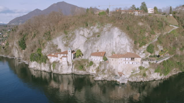 vidéos et rushes de aerial drone view of famous hermitage on lake maggiore, italy - monastère