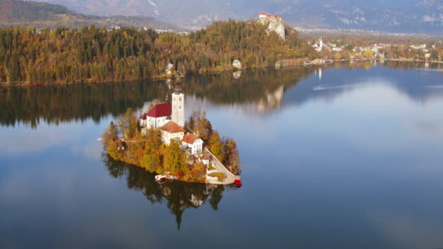 aerial drone view of famous lake bled in autumn, slovenia - lago di bled video stock e b–roll