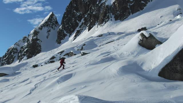 雪高山の風景、高い山々を登る女性スキーツアーの空中ドローンビュー - 冠雪点の映像素材/bロール