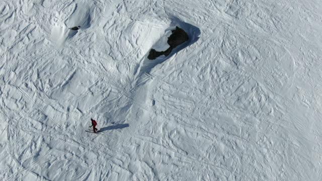 vista aerea con droni del tour sciistico femminile che si arrampica sul paesaggio alpino innevato, alte montagne sopra - bastoncino da sci video stock e b–roll