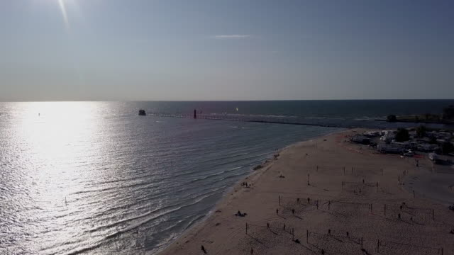 aerial drone view of  grand haven lighthouse and pier on lake michigan at sunset - michigan stock videos & royalty-free footage
