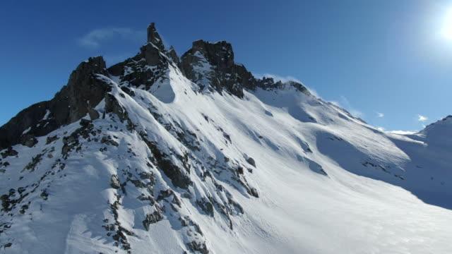 luft-drohnenansicht des hochalpinen bergrückens mit schnee bedeckt - snowcapped mountain stock-videos und b-roll-filmmaterial