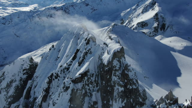 aerial drone view of high alpine mountain ridge covered in snow - snowcapped mountain stock videos & royalty-free footage