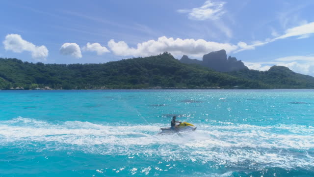 aerial drone view of jetski personal watercraft in bora bora tropical island. - bora bora aerial stock videos and b-roll footage