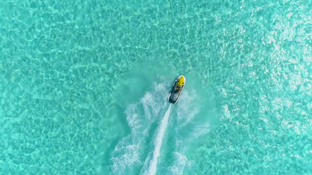 aerial drone view of jetski personal watercraft in bora bora tropical island. - jet ski stock videos & royalty-free footage
