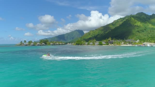 aerial drone view of jetski personal watercraft in moorea tropical island. - moorea stock videos & royalty-free footage
