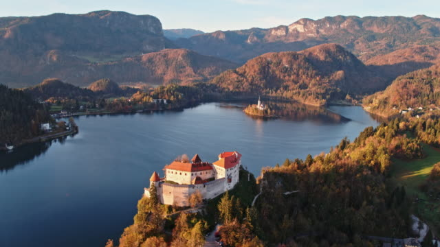 stockvideo's en b-roll-footage met aerial drone view of lake bled in autumn and bled castle, slovenia - slovenië