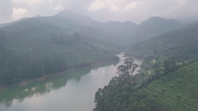 aerial drone view of lake in misty western ghats mountains of munnar, india - hill stock videos & royalty-free footage