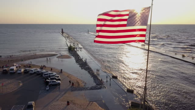 vídeos de stock, filmes e b-roll de opinião aérea do zangão do lago michigan no por do sol com a bandeira americana que voa livremente em haven sul - michigan