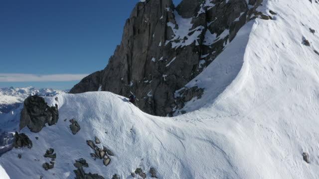 vidéos et rushes de vue aérienne de drone de grimpeur masculin montant la montagne couverte de neige raide - alpes suisses