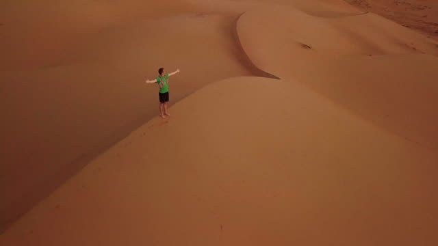 aerial drone view of man standing on top of dune with raised hands at sunrise - arms outstretched stock videos and b-roll footage