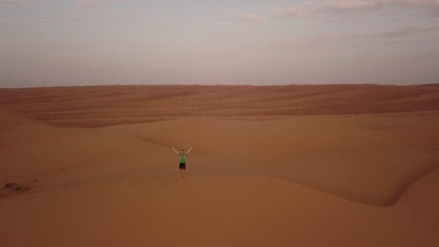 vidéos et rushes de aerial drone view of man standing on top of dune with raised hands at sunrise - découverte