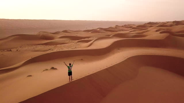 Aerial drone view of man standing on top of dune with raised hands at sunrise