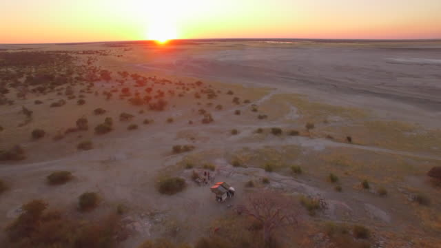 aerial drone view of men camping at a camp site with roof top tents on a pickup truck rack in africa at sunset. - tent stock videos & royalty-free footage