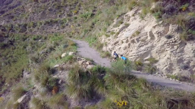 vídeos de stock e filmes b-roll de aerial drone view of men cycling and racing up a hill on bicycles, riding on road bikes in italy. - bicicleta de corrida
