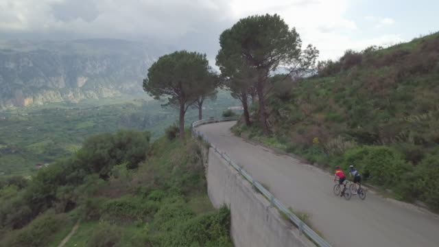 aerial drone view of men cycling and racing up a hill on bicycles, riding on road bikes in italy. - ロードサイクリング点の映像素材/bロール