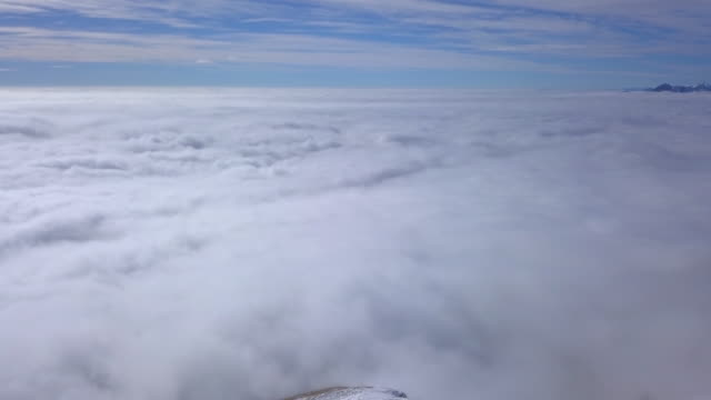 aerial drone view of men hiking in the clouds and snow covered mountains in the winter. - goodsportvideo stock videos and b-roll footage