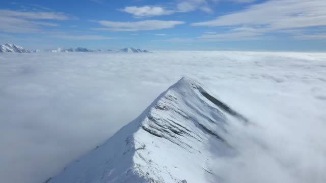 Aerial drone view of men hiking in the clouds and snow covered mountains in the winter.