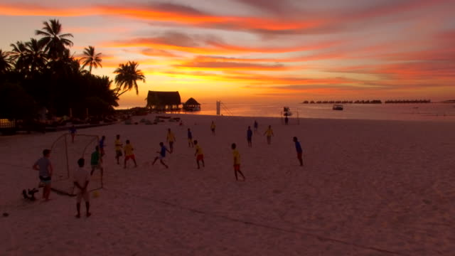 vídeos de stock, filmes e b-roll de aerial drone view of men playing soccer football on the beach of a tropical island at sunset. - esporte de equipe