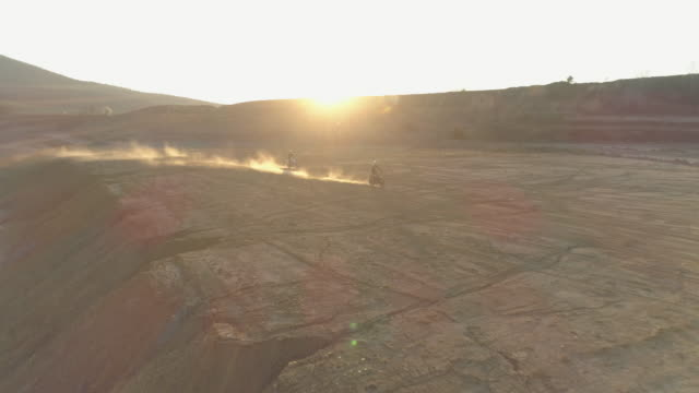 aerial drone view of men racing motocross motorcycles on a dirt off road. - off road racing stock videos & royalty-free footage