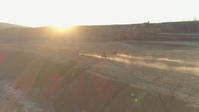 aerial drone view of men racing motocross motorcycles on a dirt off road at sunset. - slow motion - dirt track stock videos & royalty-free footage